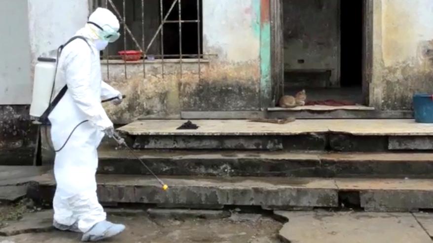 Ein Mann in Schutzkleidung reinigt eine Steintreppe.