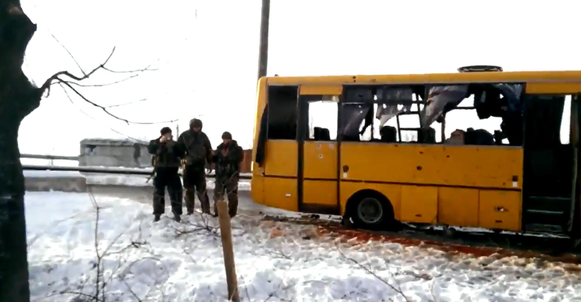 Ein gelber, zerbombter Bus steht auf einer Straße.