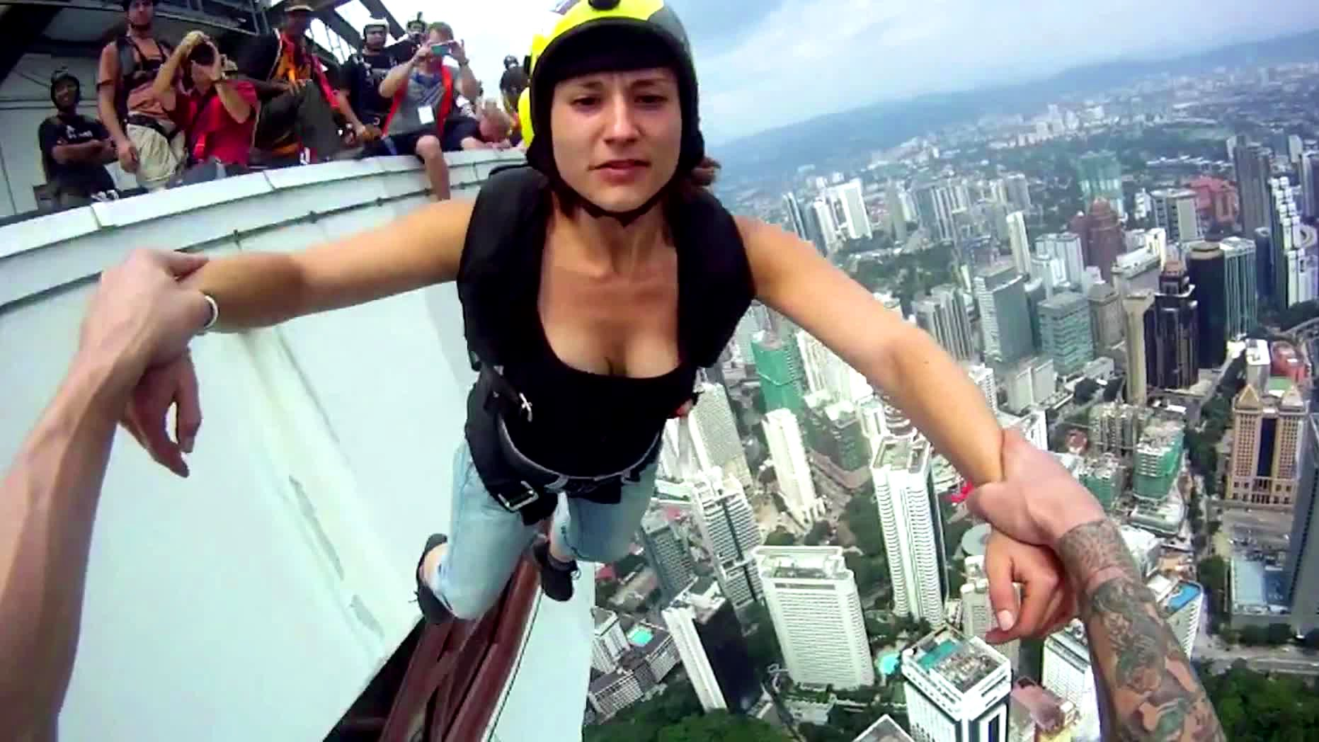 Eine BASE-Jumperin springt von einem Turm.