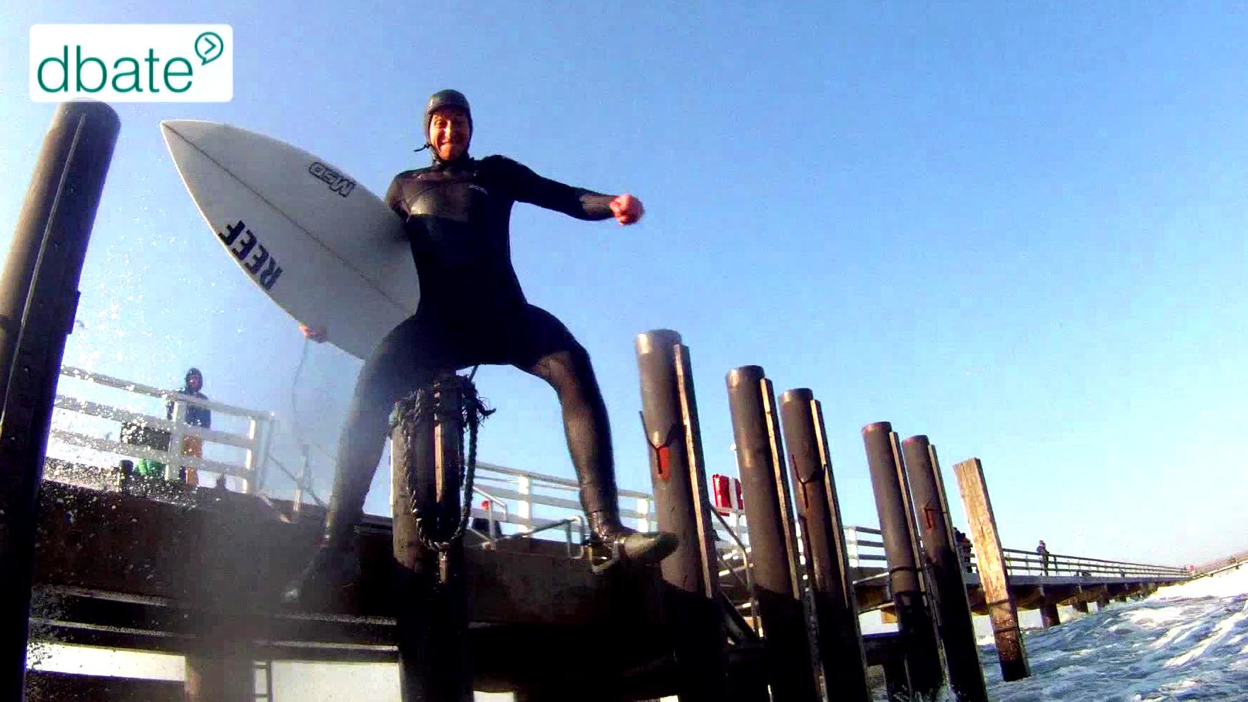 Ein Surfer springt in Neoprenanzug ins Wasser.