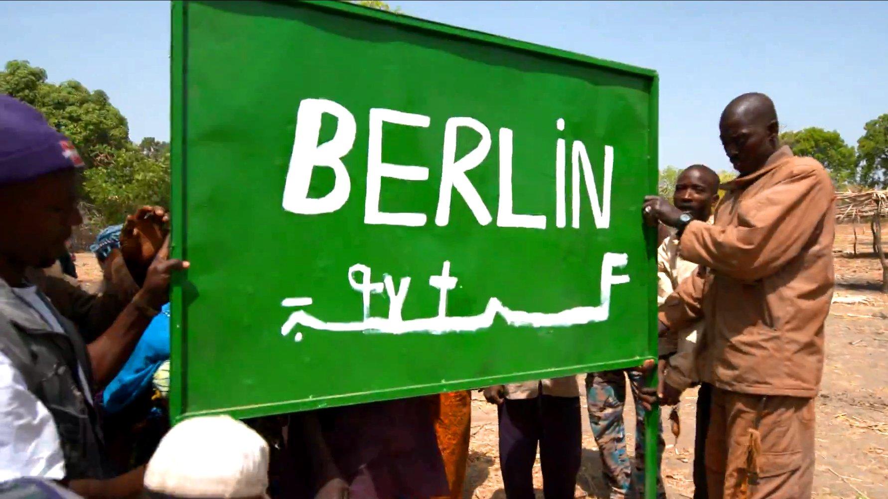 Bewohner von Berlin in Guinea halten ein Ortsschild hoch.