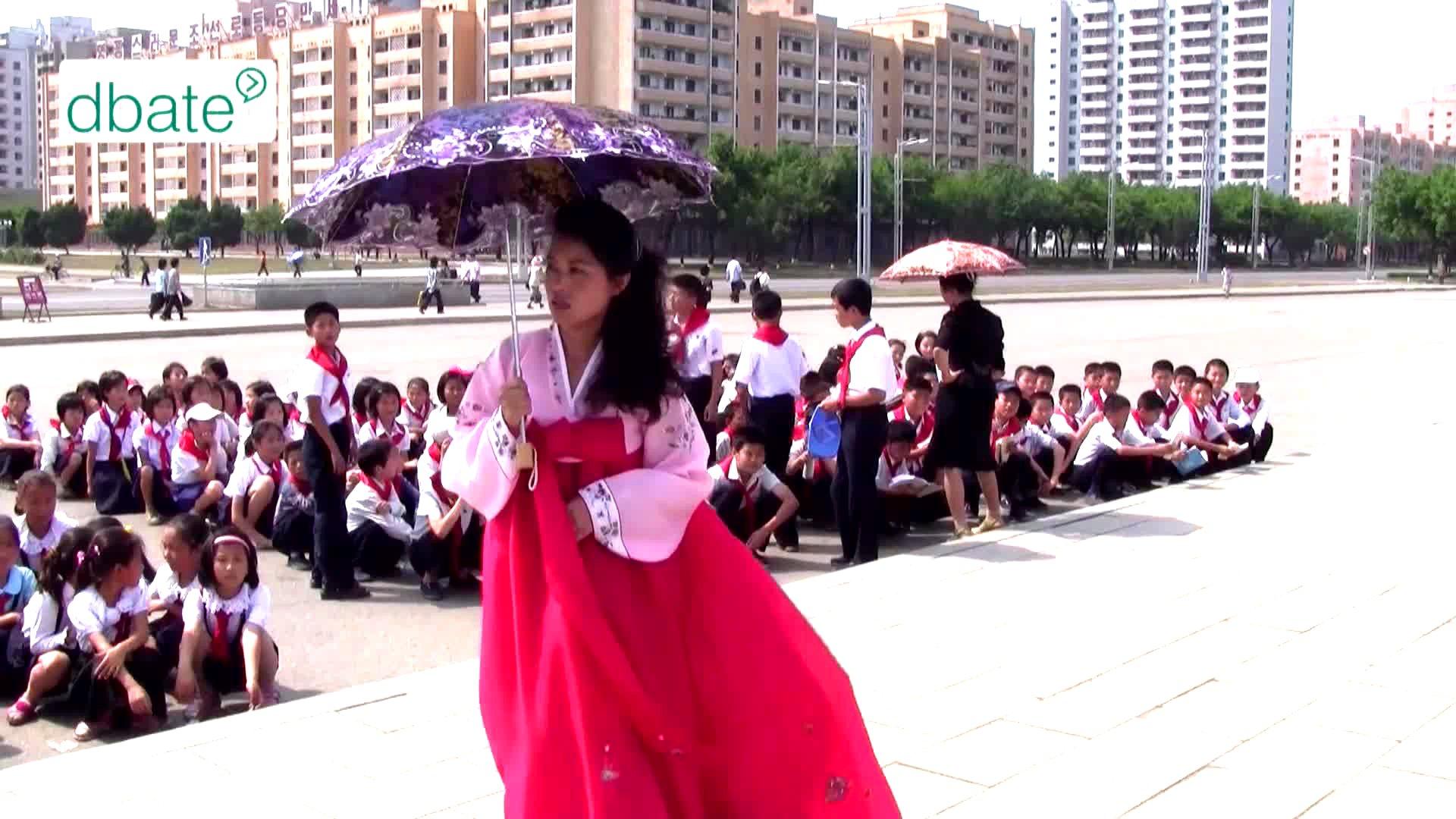 Eine junge Frau steht in Nordkorea auf einem Platz.