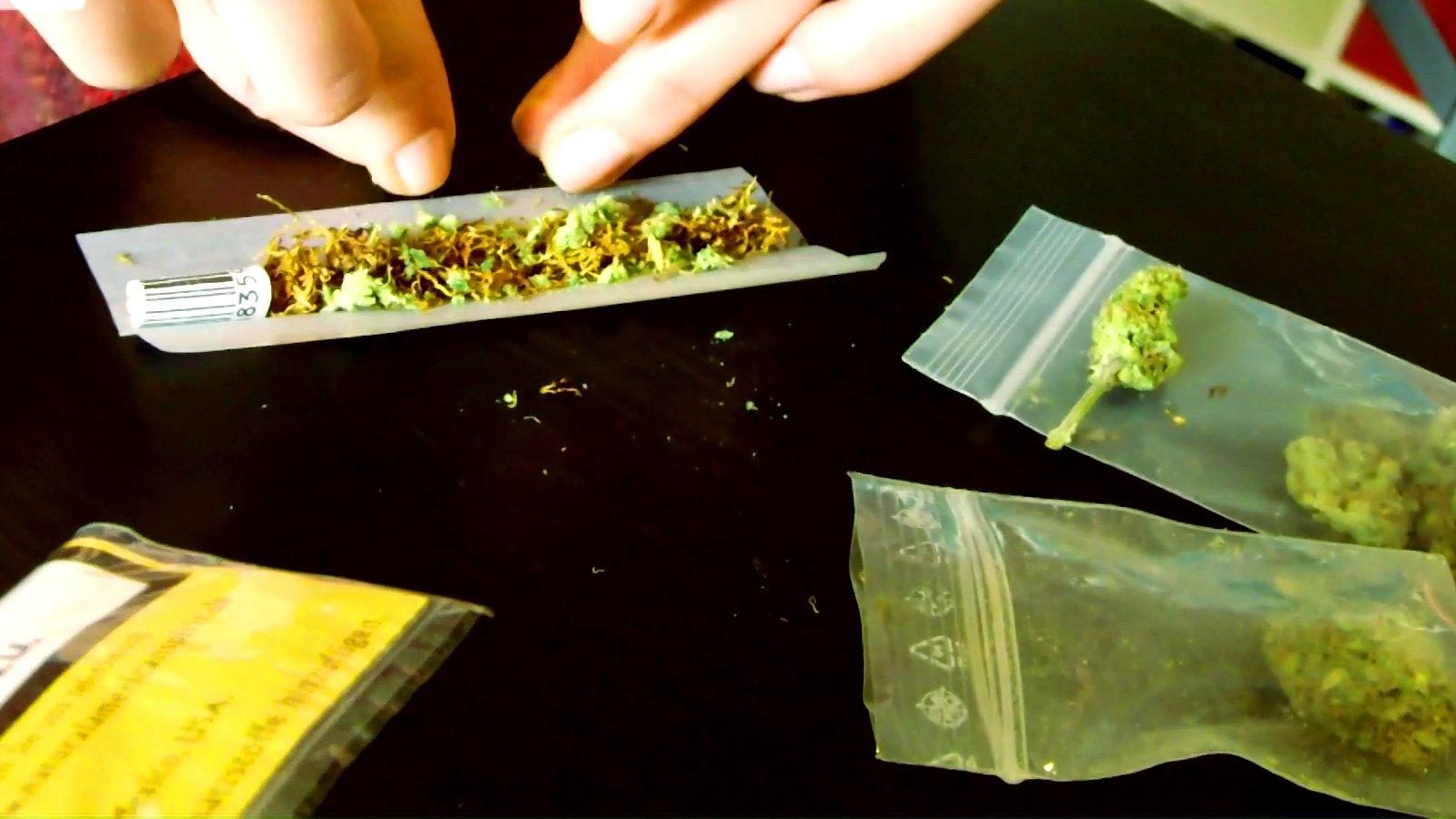 Eine Frau dreht einen Joint mit Cannabis und Tabak.