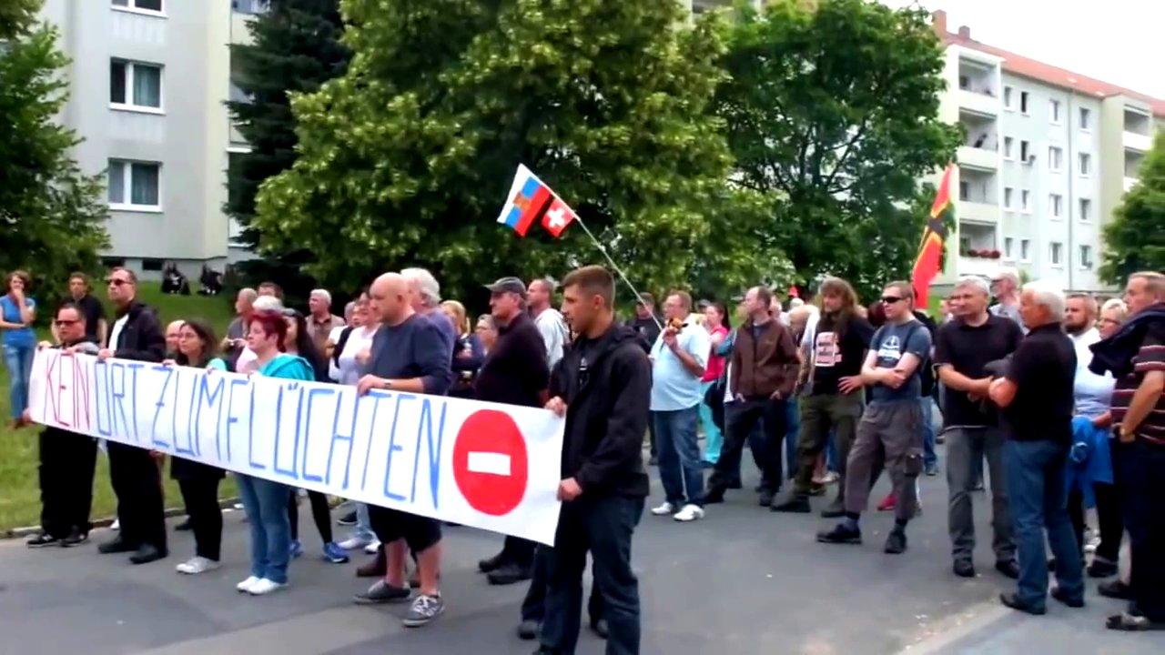 Demonstranten in Freital demonstrieren gegen Flüchtlinge und halten Plakate hoch
