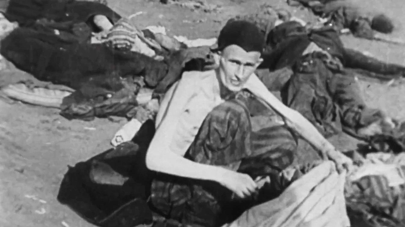 Ein Jude sitzt im KZ-Auschwitz-Birkenau vor Leichen auf dem Boden.
