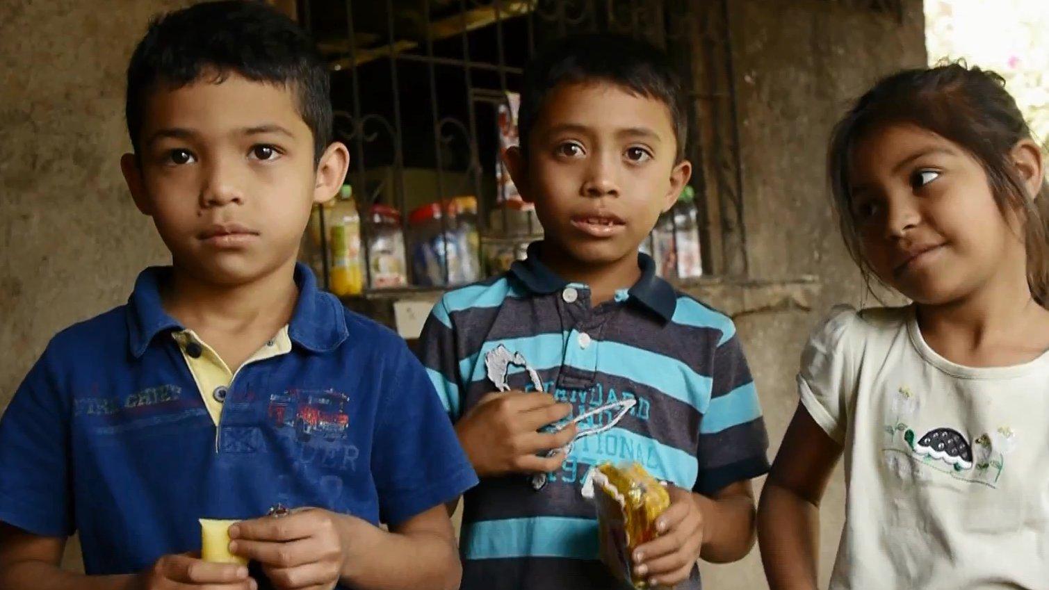 Drei Kinder schauen vor einem Kiosk in die Kamera.
