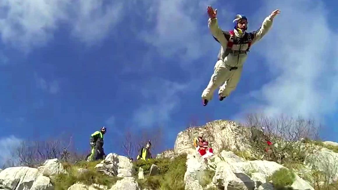 Ein Base-Jumper springt von einem Berg.