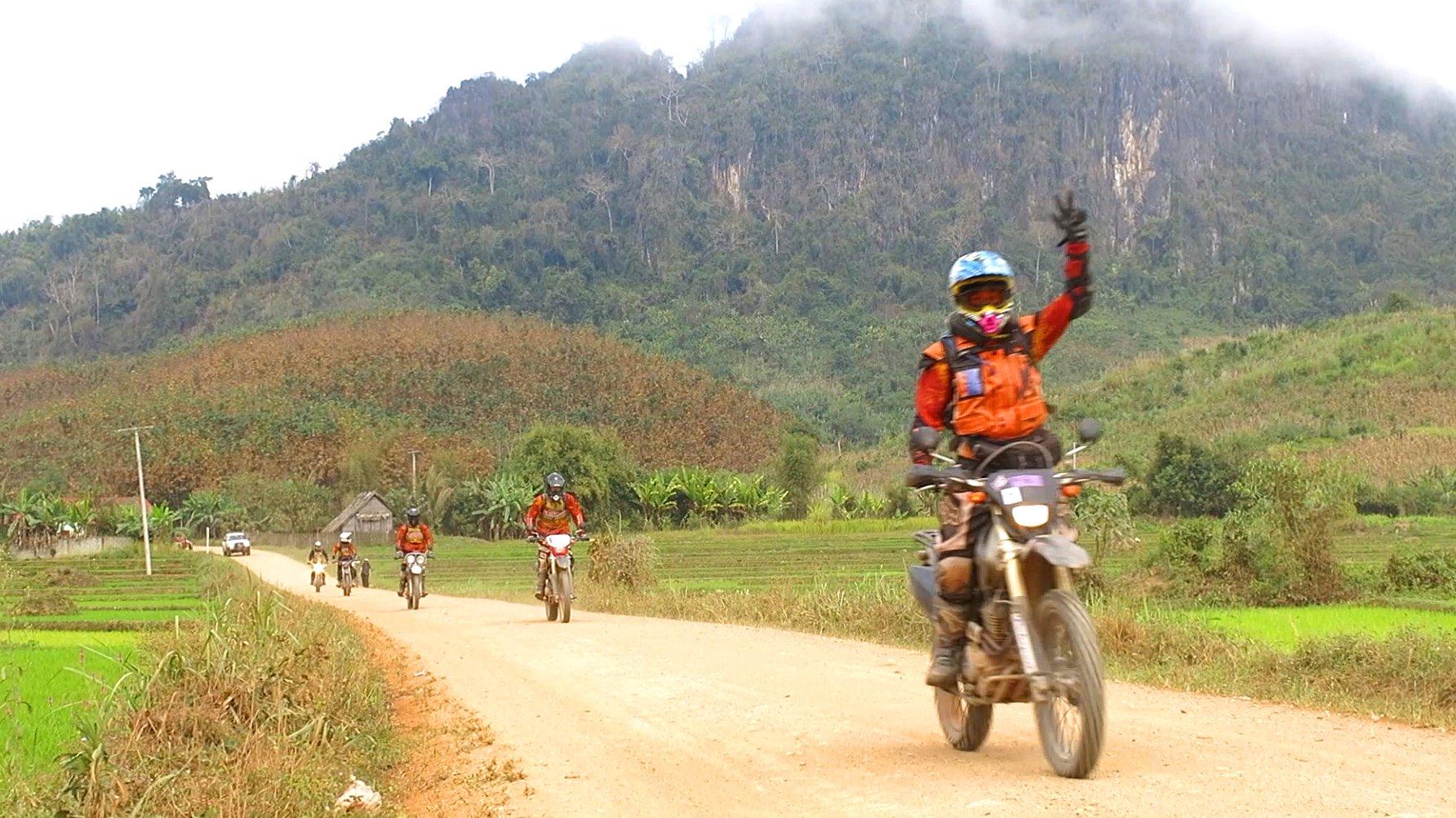 Ein Mottoradfahrer fährt eine Straße in Laos entlang.