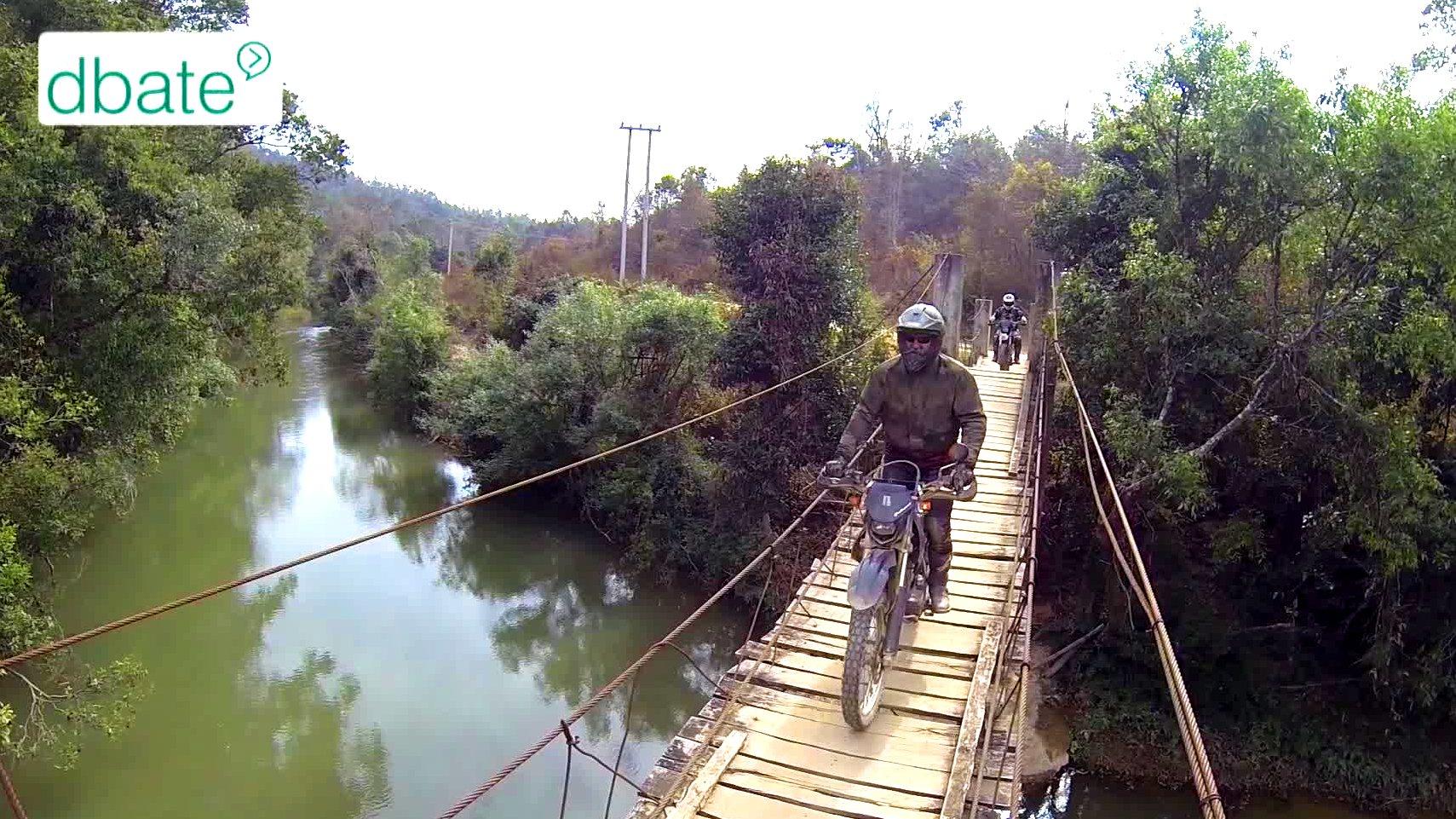 Ein Motorradfahrer fährt in Laos über eine Holzbrücke.