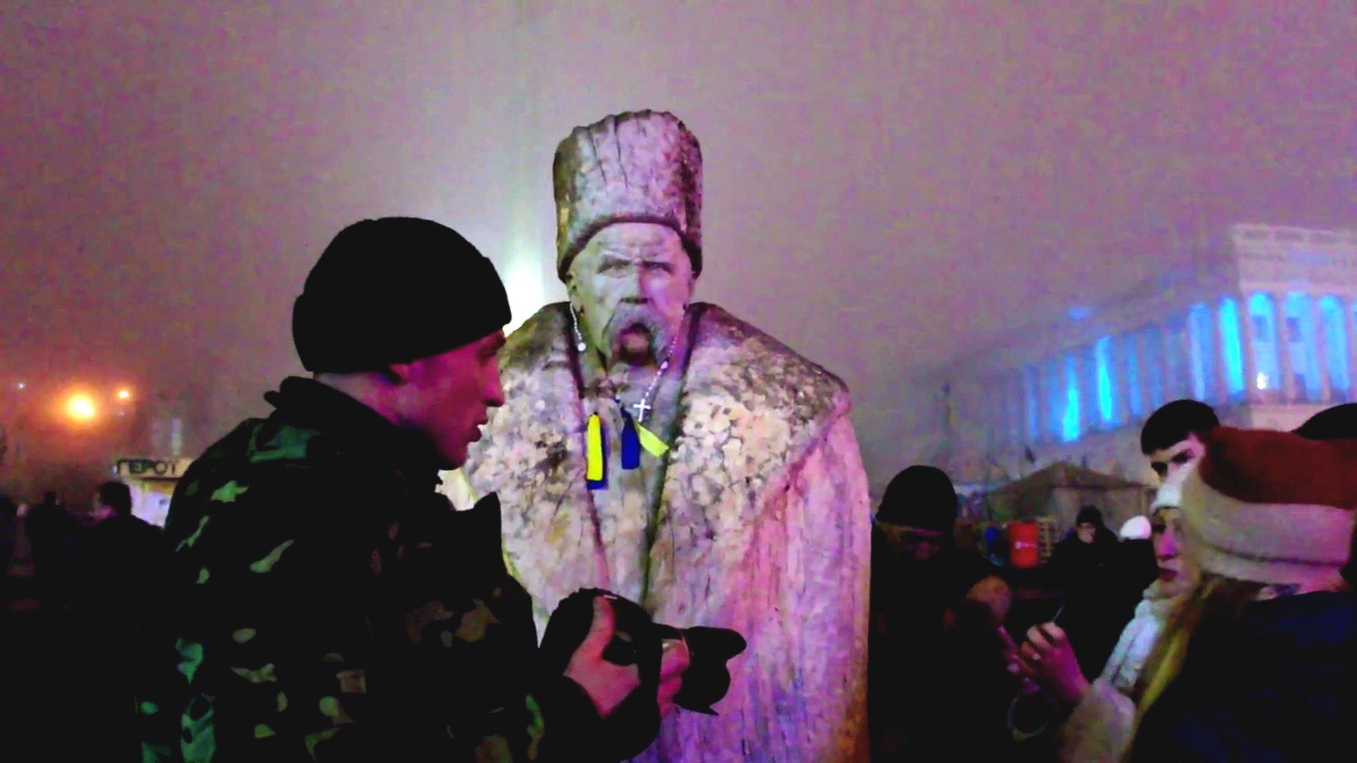 Mann steht vor Statue in Kiew